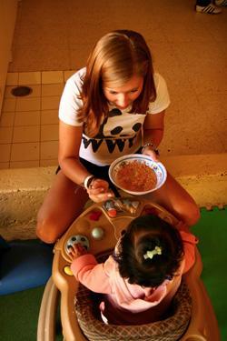 Vapaaehtoinen syöttää lasta päiväkodissa