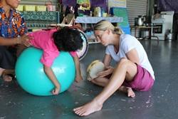 Fysioterapia-vapaaehtoinen auttaa lasta Samoalla